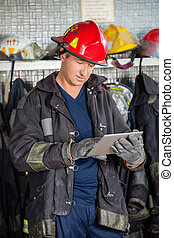 Firefighter Using Digital Tablet At Fire Station - Mature...