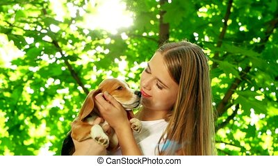 gir playing with her beagle dog in summer park Slow motion -...