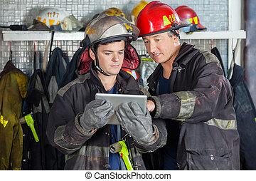 Firefighters Discussing Over Digital Tablet - Male...