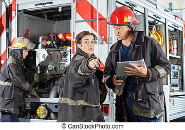 Firefighter Pointing While Colleague Holding Digital Tablet...