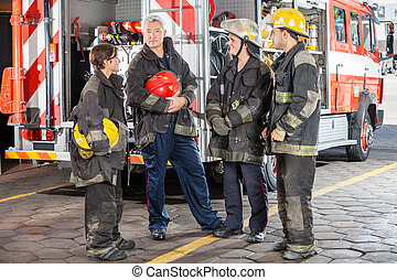 Portrait Of Confident Firefighter Standing With Team - Full...