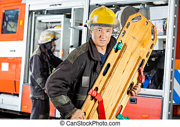 Confident Firefighter Holding Wooden Stretcher - Confident...