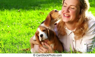happy woman with a dog beagle playing on nature. Close up