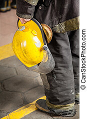 Fireman Holding Helmet At Fire Station - Low section rear...