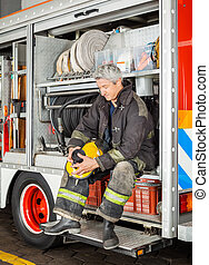Fireman Holding Coffee Cup While Sitting In Truck - Full...