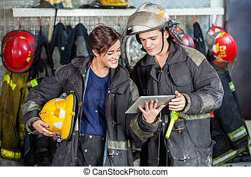 Firefighters Using Digital Tablet At Fire Station - Young...