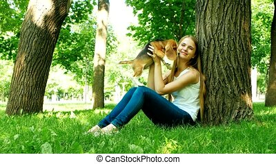 happy girl with a dog beagle playing on nature