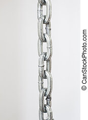 part of metal chrome chain against light grey background