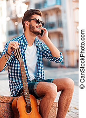 Waiting for friends. Low angle view of cheerful young man holding guitar and talking on the mobile phone while sitting outdoors