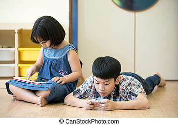 Little Asian boy and girl are playing together with a...