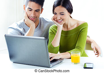 Happy young couple browsing internet at home - Portrait of...