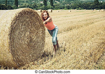 Smiling woman pushing the haystack and having fun by harvest