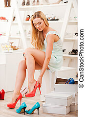 I hope they will fit. Beautiful young woman trying on different shoes while sitting in shoe store