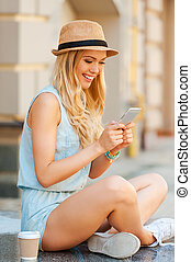 Keeping in touch with her friends. Side view of young woman...