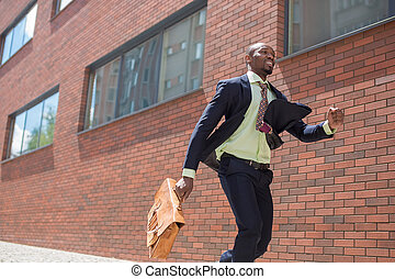 african black young businessman running in a city street