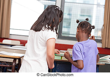 Multi Racial classroom with children collaborating in primary school