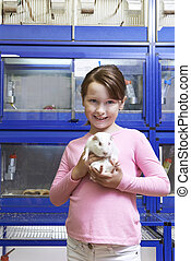 Girl Holding Guinea Pig In Pet Store
