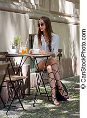 Tasty refreshments. - Stylish young brunette beauty having...