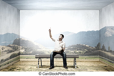 Fat man sitting on bench with book and pointing with finger