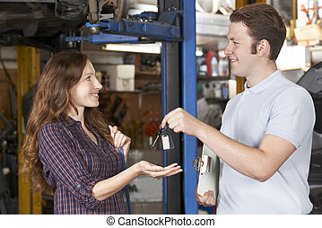 Satisfied Customer Collecting Car From Garage Mechanic