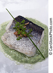 cooked fish with green sauce on white plate