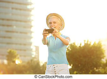 Happy smiling young woman taking selfie portrait outside