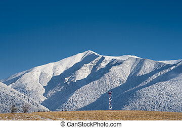 GSM tower in mountains - GSM tower on a field with white...
