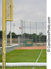 Foul post behind outfield at baseball diamond - Behind the...