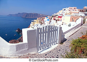 Entrance white gate with the buildings, Oia, Santorini,...