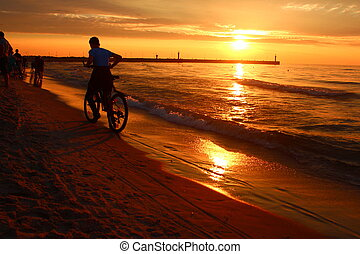 Evening relaxation on the Baltic. - Young man on a bicycle...