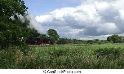 Steam train riding in countryside - cumulus clouds