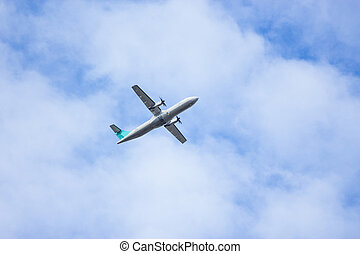 The plane high in the blue sky picks up speed
