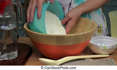 Female pour the flour and sugar in the bowl