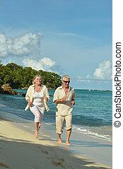 Elderly couple running on beach - Happy elderly couple...