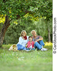 Family with apples and book in park