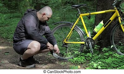 Man with pump near bicycle tire
