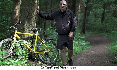 Man warm up near bicycle in the park