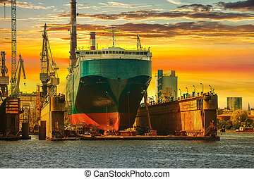 Ship in dry dock - Ship being repaired in dry dock at sunset...