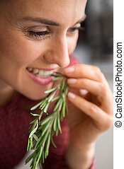 Closeup of smiling woman tasting fresh rosemary - A woman...