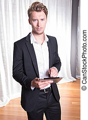 Portrait young business man in suit working with tablet