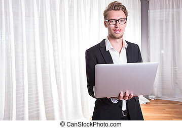 Portrait young business man in suit working with laptop