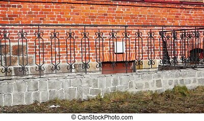 Red brick house wall and fence