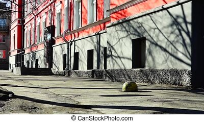 Old red building on street tilt - Old red building with...