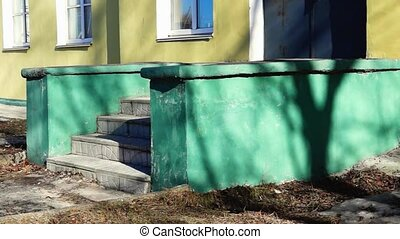 Stairs of old yellow building in sunny spring day