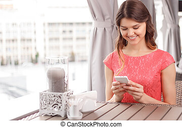 Pretty young woman using mobile phone in cafe