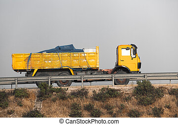 Dump truck on the road - Yellow dump truck on the road with...