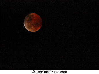 Red Moon Rising - Full lunar eclipse casts a red glow on the...