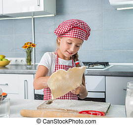 little girl rolling out a dough