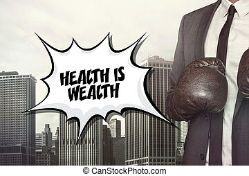 Health is wealth text with businessman wearing boxing gloves...