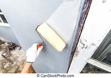 hand glove holding paint brush while painting home wall